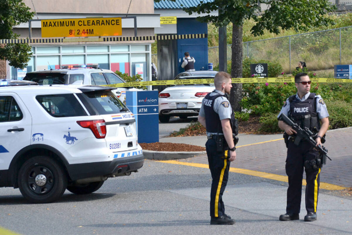 Police officers stand in a cordoned-off portion of the parking lot at Southpoint Exchange in South Surrey, in front of the drive-thru lane where Suminder (Ali) Grewal was fatally shot on Aug. 2, 2019. (Nick Greenizan file photo)