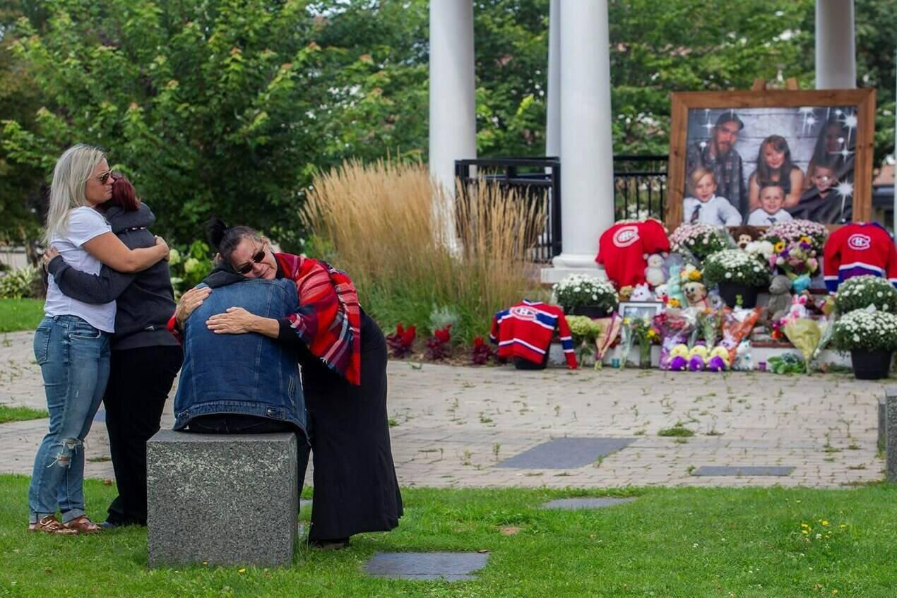 People gather at a memorial site in Amherst, N.S. on Tuesday Sept. 14, 2021. A Nova Scotia town is grieving the loss of a family of six, including four children, whose bodies were discovered Sunday evening following a fire in a travel trailer. THE CANADIAN PRESS/Ron Ward