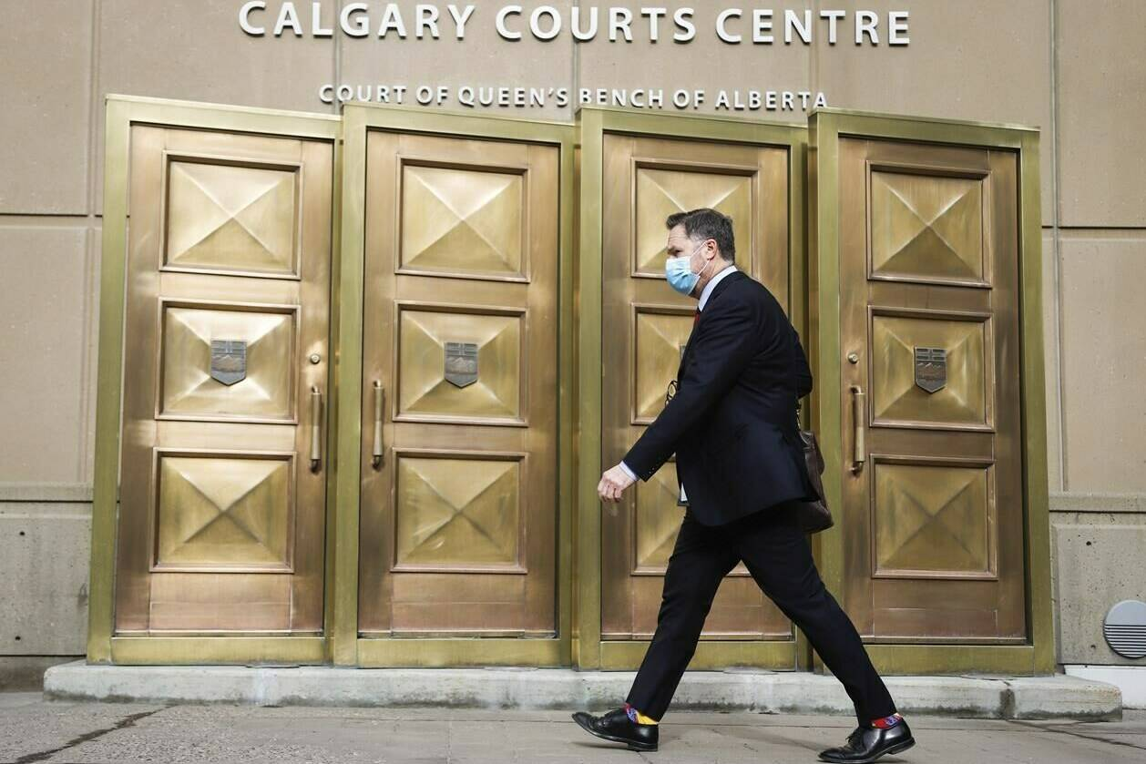 A man wears a mask as he enters the Calgary Courts Centre during COVID-19 restrictions on Monday, May 17, 2021. THE CANADIAN PRESS/Jeff McIntosh