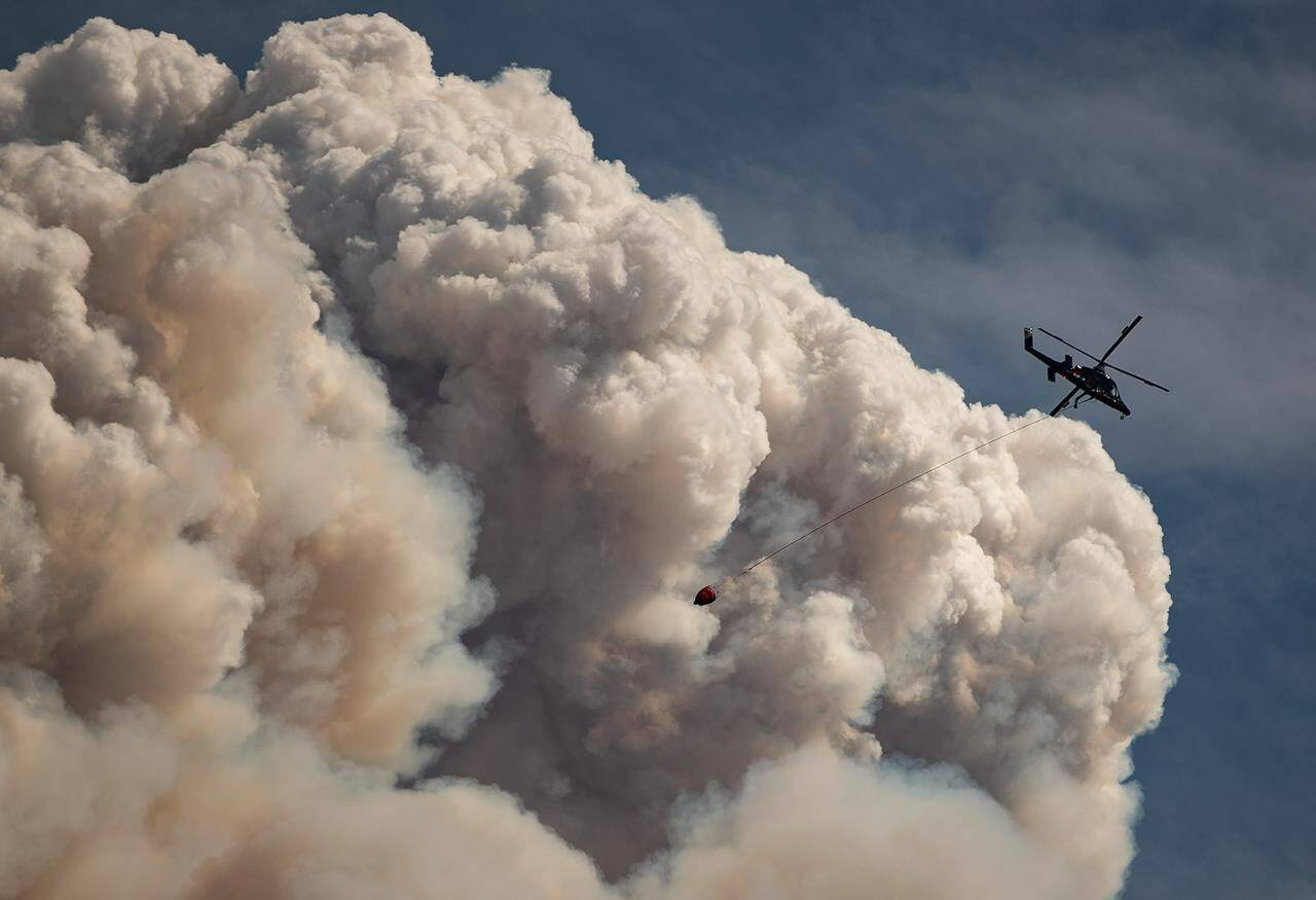 A helicopter carrying a water bucket flies past a pyrocumulus cloud, also known as a fire cloud, produced by the Lytton Creek wildfire burning in the mountains above Lytton, B.C., on Aug. 15, 2021. (Darryl Dyck/Canadian Press)
