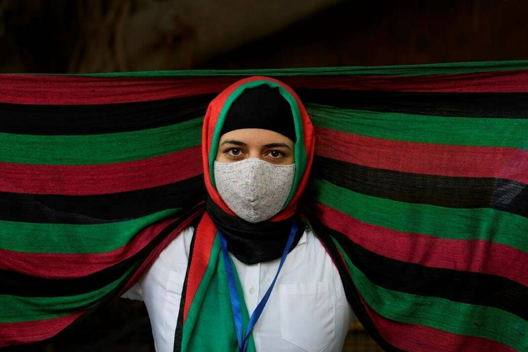 FILE - In this Aug. 23, 2021, file photo, an Afghan refugee living in India wearing a scarf in the colors of Afghanistan flag participates in a protest against the Taliban takeover of Afghanistan outside the office of United Nation High Commissioner for Refugees, in New Delhi, India. India's leaders are anxiously watching the Taliban takeover in Afghanistan, fearing that it will benefit their bitter rival Pakistan and feed a long-simmering insurgency in the disputed region of Kashmir, where militants already have a foothold. (AP Photo/Manish Swarup, File)