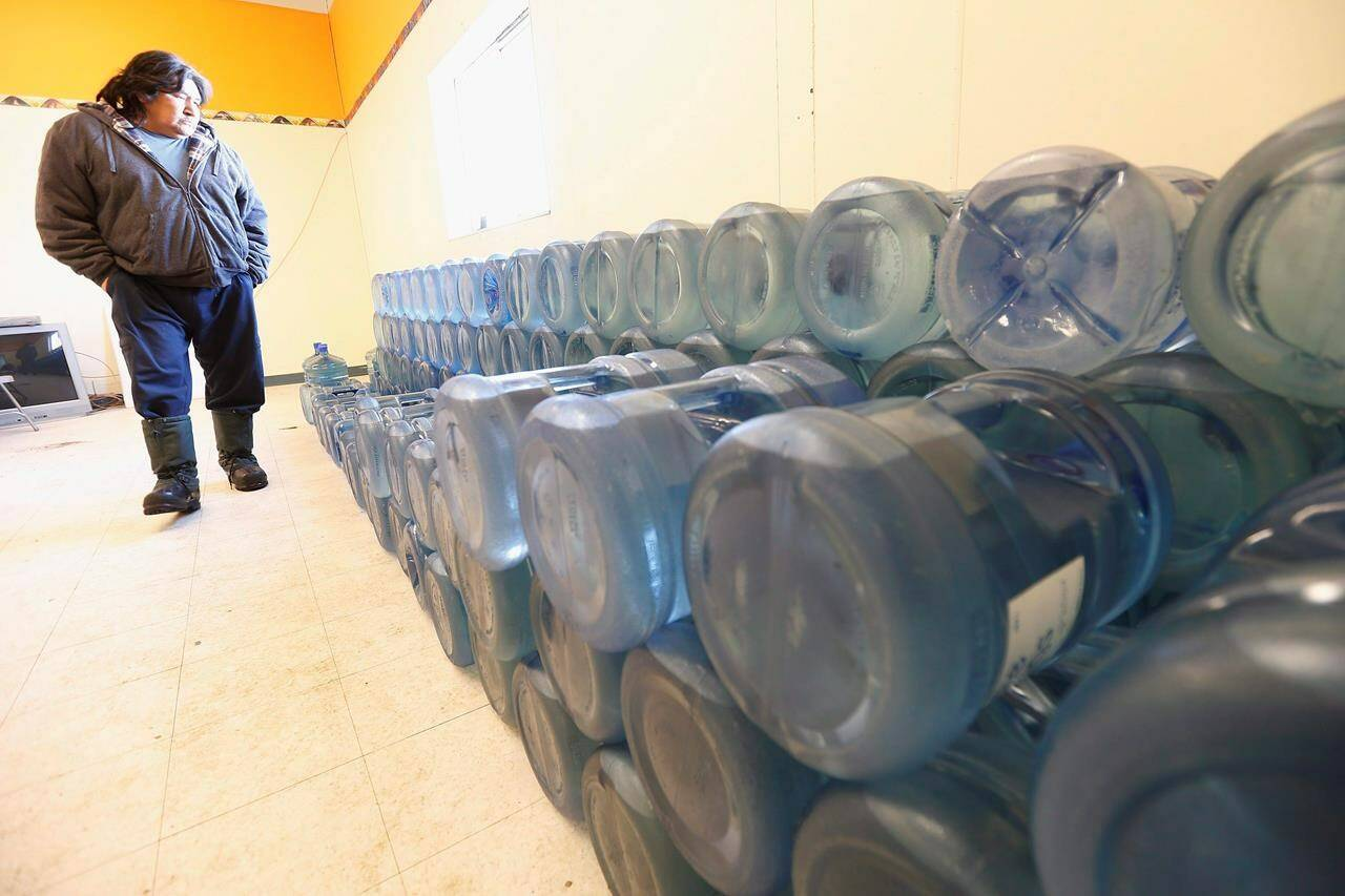 Stewart Redsky, former chief of Shoal Lake 40 First Nation, walks past one week's worth of 20 litre water bottles in the community's water storage room on Feb. 25, 2015. The First Nation is now welcoming clean, running water for the first time in nearly 25 years. THE CANADIAN PRESS/John Woods