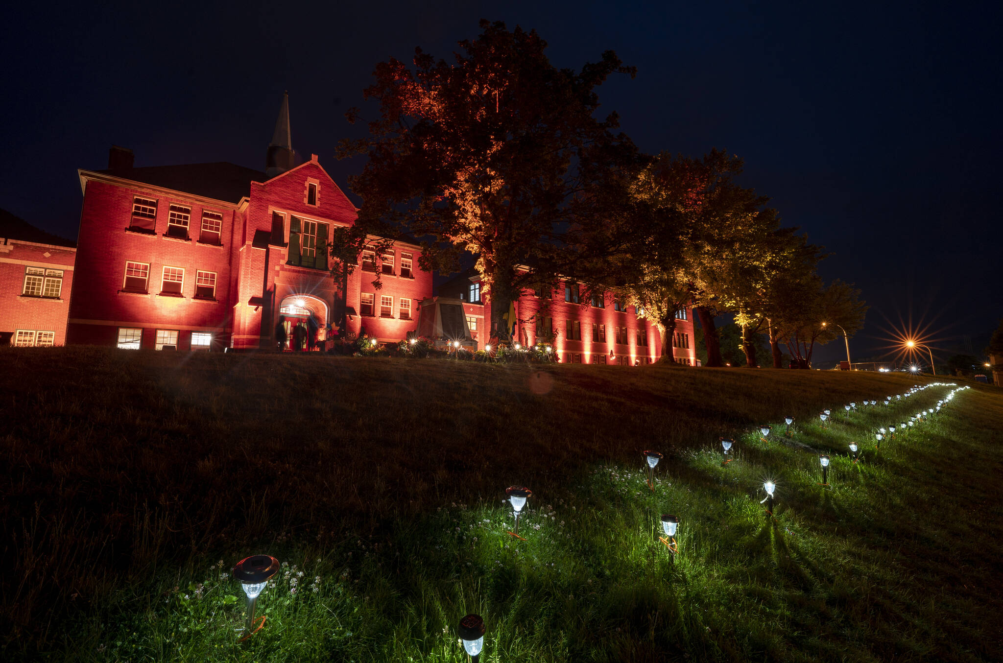 Two hundred and fifteen lights are placed on the lawn outside the Residential School in Kamloops, B.C., Saturday, June, 13, 2021. The remains of 215 children were discovered buried near the former Kamloops Indian Residential School earlier this month. THE CANADIAN PRESS/Jonathan Hayward