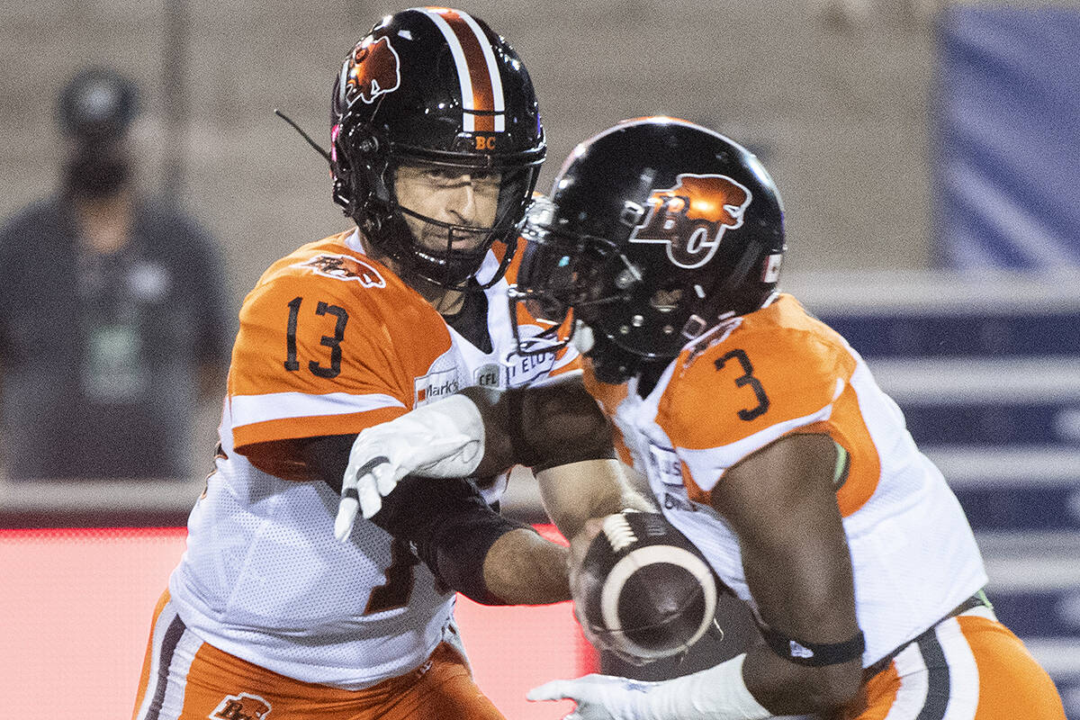 B.C. Lions quarterback Michael Reilly (13) hands off to running back Chris Rainey (3) during first half CFL football action against the Montreal Alouettes in Montreal, Saturday, September 18, 2021. THE CANADIAN PRESS/Graham Hughes