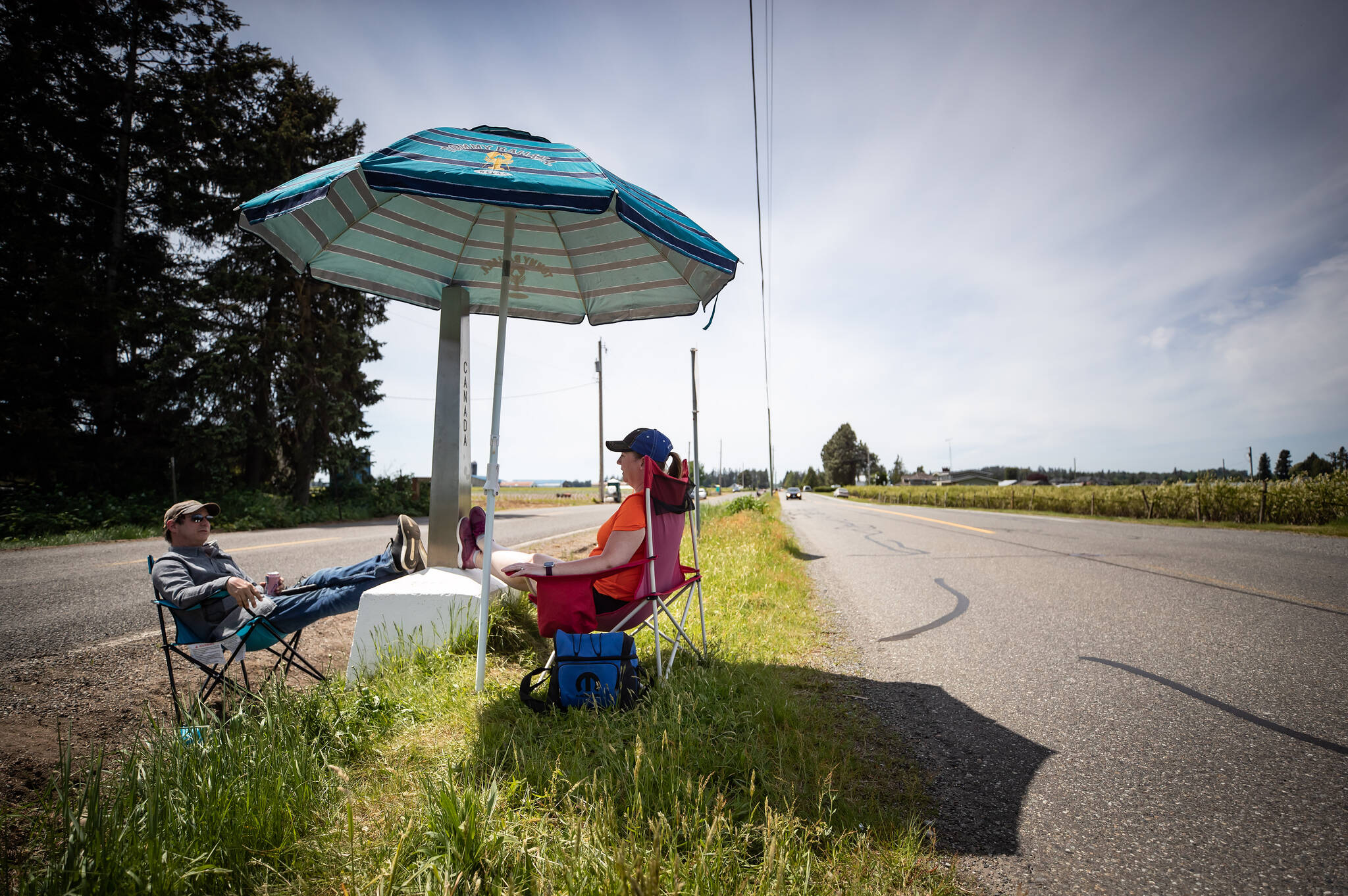 Engaged couple Rob Sensel, left, of Mount Vernon, Wash., and Kathryn Bell Lewis, of Richmond, B.C., spend time together separated by a ditch along the Canada-U.S. border, in Abbotsford, B.C., on Sunday, May 10, 2020. The closure of the Canada-U.S. border to non-essential travel has been extended another month, the U.S. announced Sept. 20. THE CANADIAN PRESS/Darryl Dyck