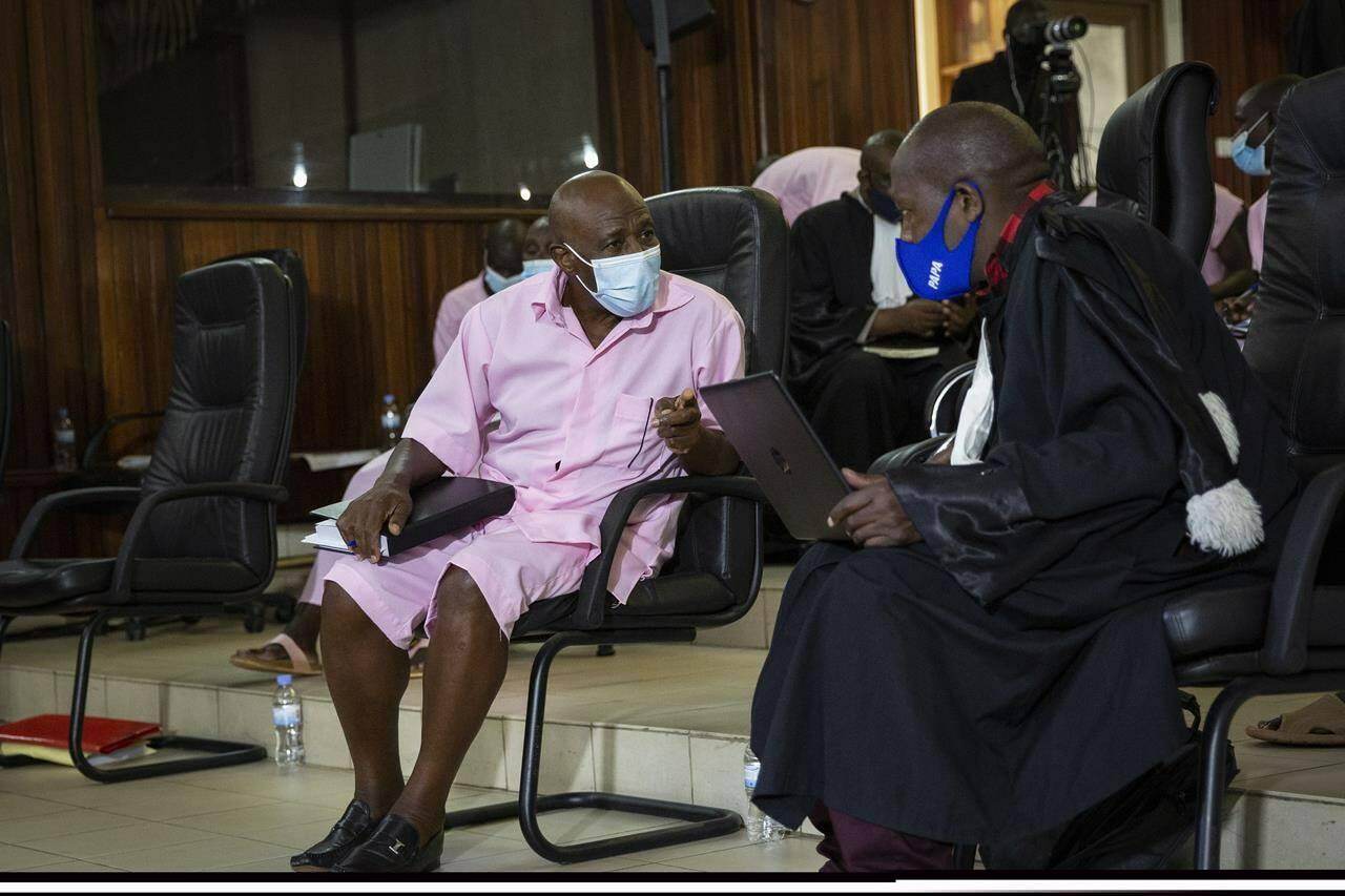 """FILE - In this Friday, Feb. 26, 2021 file photo, Paul Rusesabagina, whose story inspired the film """"Hotel Rwanda"""" for saving people from genocide, speaks to lawyers as he attends a court hearing in Kigali, Rwanda. A court in Rwanda said Monday, Sept. 20, 2021 that Rusesabagina, who boycotted the announcement after declaring he didn't expect justice in a trial he called a """"sham"""", is guilty of terror-related offenses. (AP Photo/Muhizi Olivier, File)"""