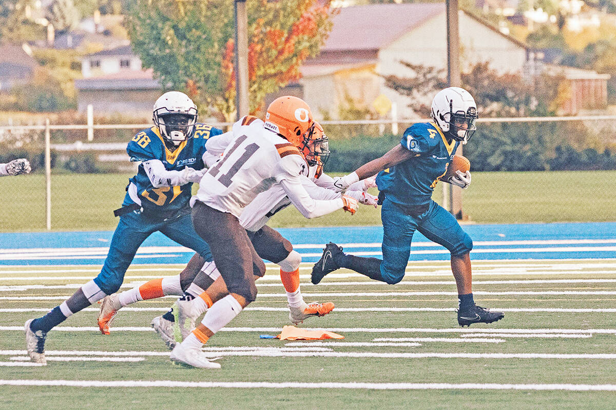 Rams wide receiver Daniel Kubongo carries the ball against the Sun during the team home opener at McLeod Athletic Park with defensive back Michael Bachuoch coming up from behind on Sunday, Sept. 19. (Honey Mustard Media/special to Langley Advance Times)