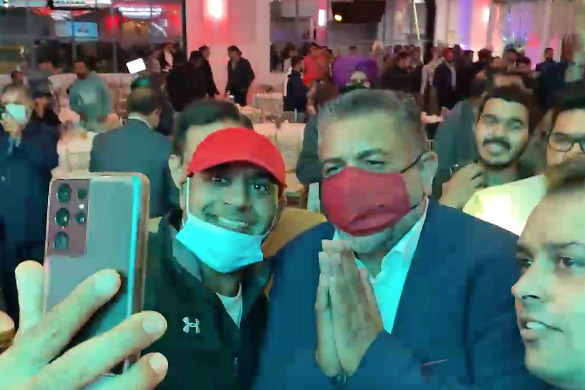 """Surrey-Newton Liberal candidate Sukh Dhaliwal (right, wearing red mask) poses for a supporter's """"selfie"""" photograph during an election-night event Monday (Sept. 20) at The Grand Taj Banquet Hall in Surrey. (photo from video: Tom Zillich)"""