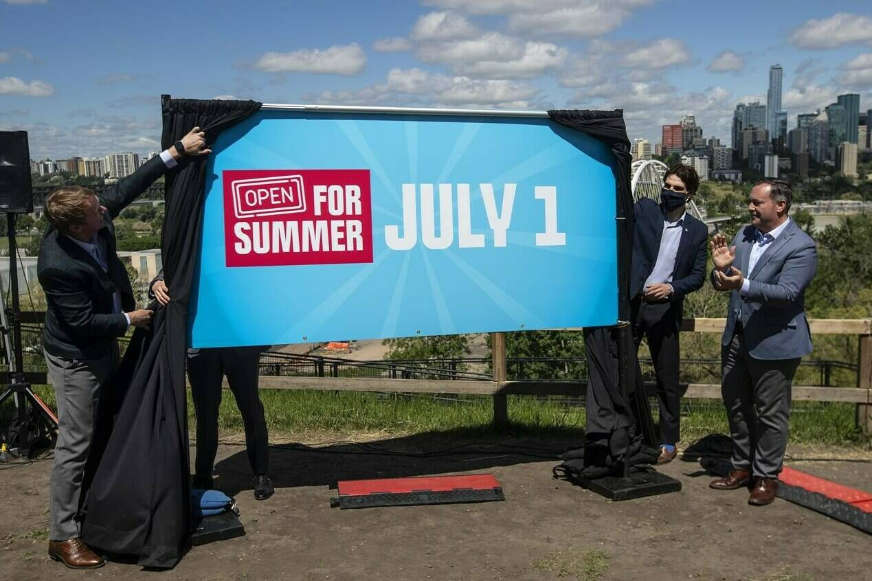 Albert Health Minister Tyler Shandro and Alberta Premier Jason Kenney unveil an opening sign after speaking about the Open for Summer Plan and next steps in the COVID-19 vaccine rollout, in Edmonton on June 18, 2021. THE CANADIAN PRESS/Jason Franson