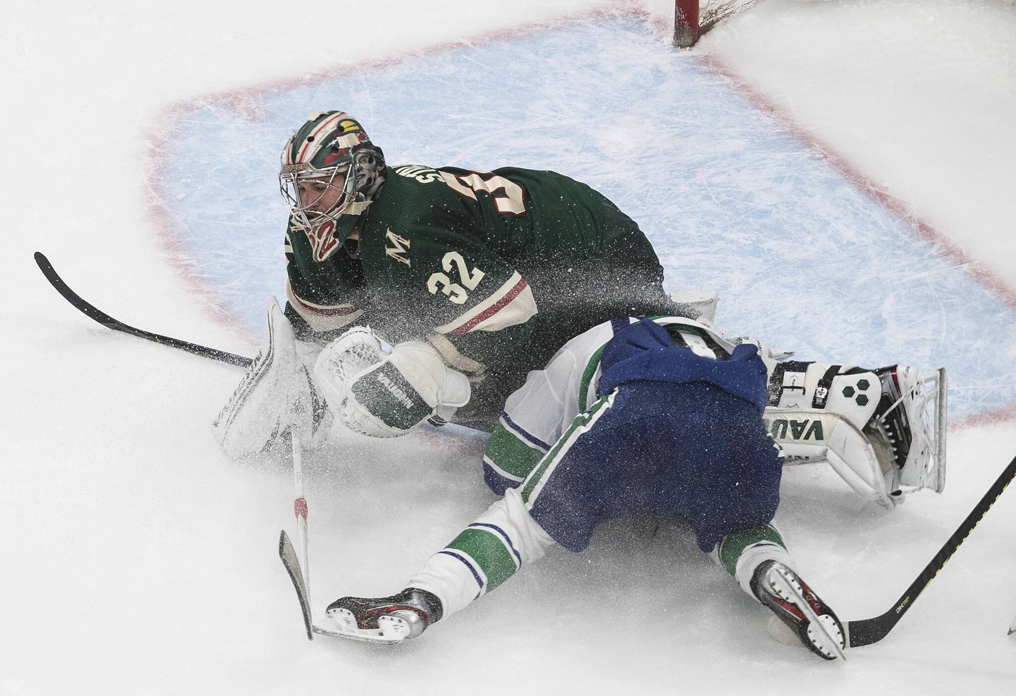 Vancouver Canucks' Elias Pettersson (40) slides into then-Minnesota Wild goaltender Alex Stalock (32) during third period NHL qualifying round game action in Edmonton, on Friday August 7, 2020. THE CANADIAN PRESS/Jason Franson