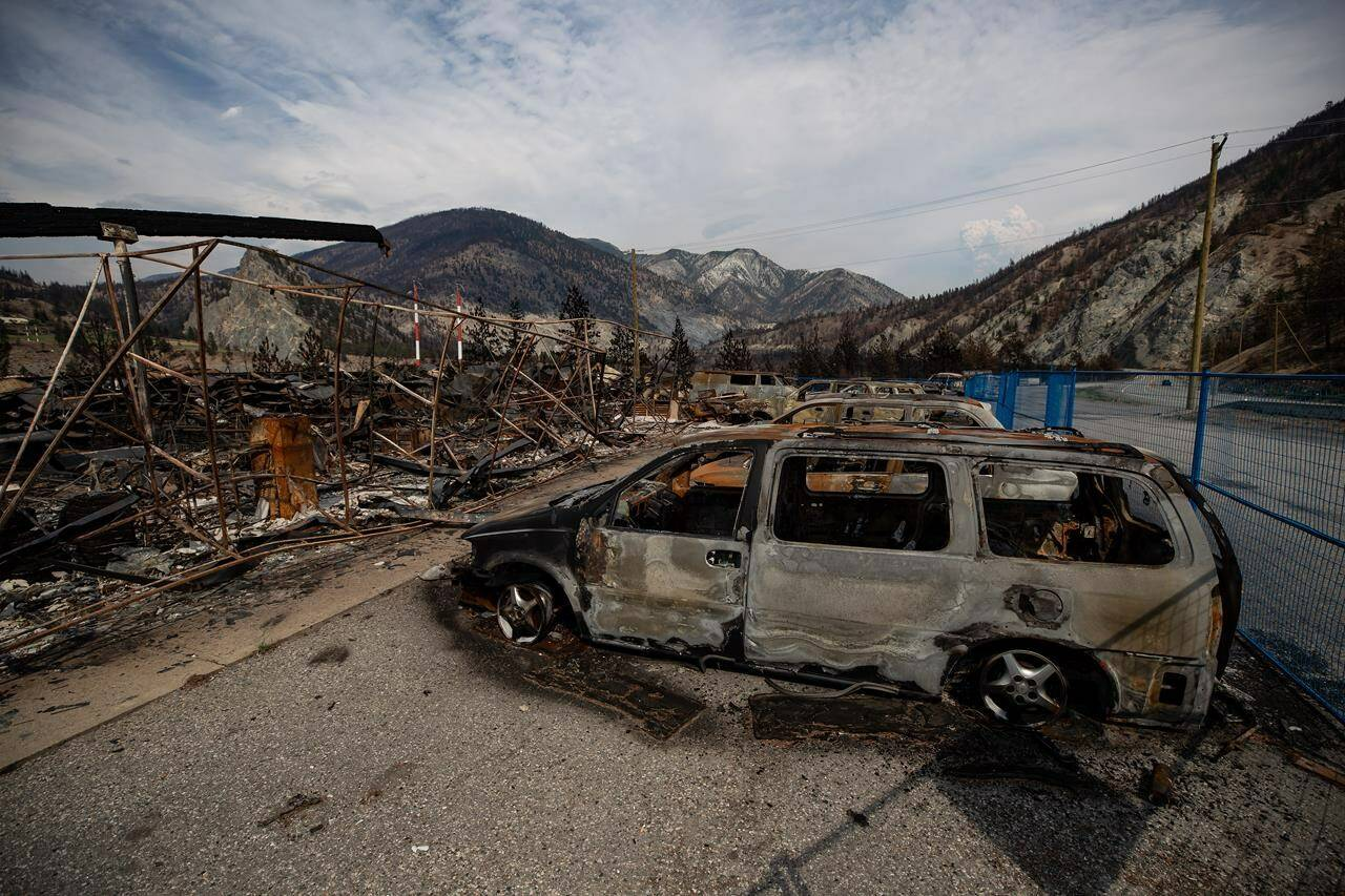 The remains of a large structure and vehicles destroyed by the Lytton Creek wildfire are seen on the side of the Trans-Canada Highway near Lytton on Aug. 15, 2021. (THE CANADIAN PRESS/Darryl Dyck)