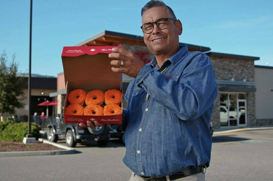 Tim Hortons franchise co-owner, former Tkemlups te Secwepemc First Nation chief and former B.C. regional chief for the Assembly of First Nations Shane Gottfriedson holds a box of orange-sprinkled Tim Hortons doughnuts in this undated handout photo taken from video. The discovery of the unmarked graves of children, some as young as three years old, sent shockwaves across the country last spring. It also propelled a group of Indigenous Tim Hortons owners to come up with fundraising campaign for residential school survivors involving an orange-sprinkled doughnut. THE CANADIAN PRESS/HO, Tim Hortons *MANDATORY CREDIT*
