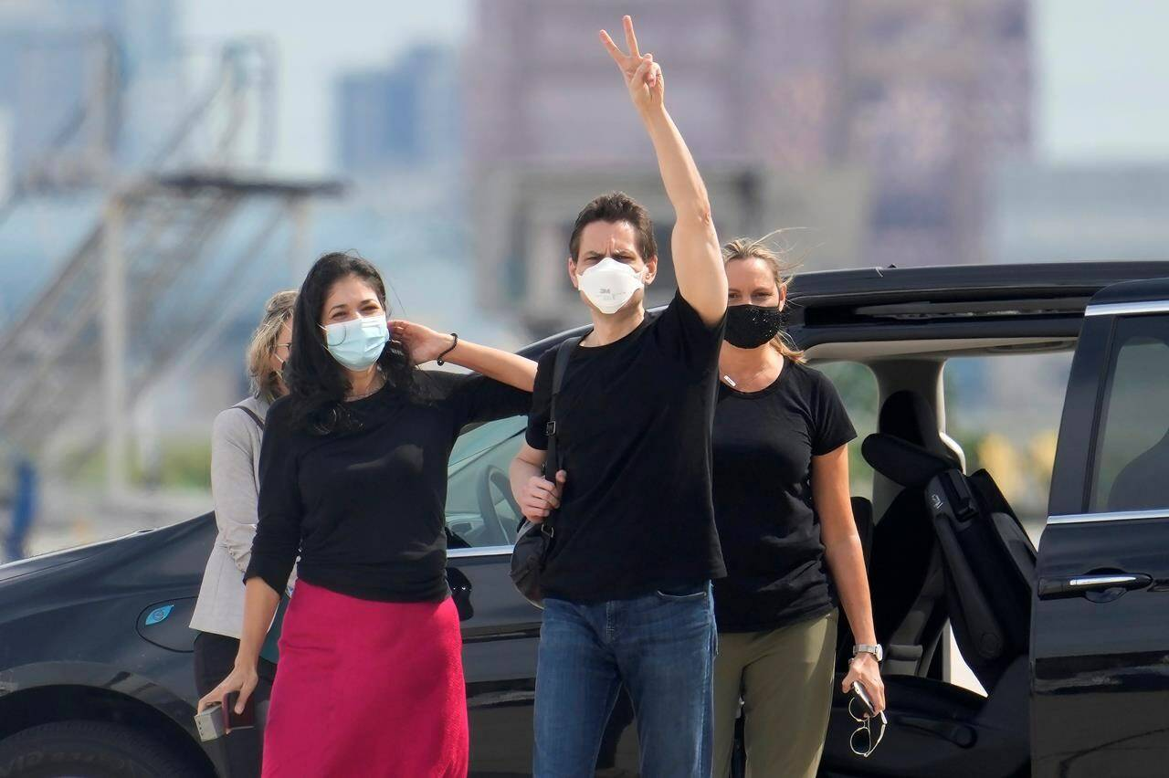 Michael Kovrig, centre right, waves to media as his wife Vina Nadjibulla, centre left, and sister Ariana Botha after his arrival at Pearson International Airport in Toronto on September 25, 2021. THE CANADIAN PRESS/Frank Gunn