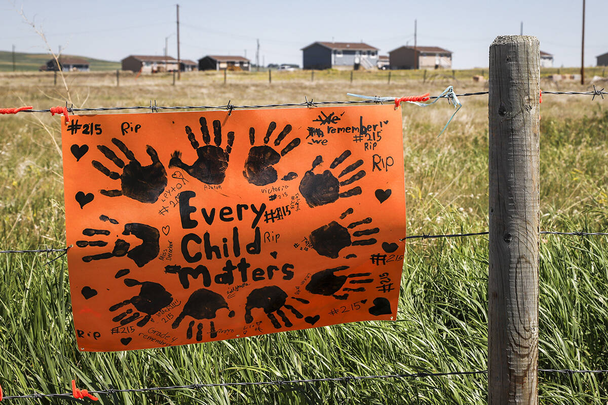 A sign commemorating victims of residential schools is attached to a fence line in front of homes on the Siksika First Nation, east of Calgary near Gliechen, Alta., Tuesday, June 29, 2021. THE CANADIAN PRESS/Jeff McIntosh