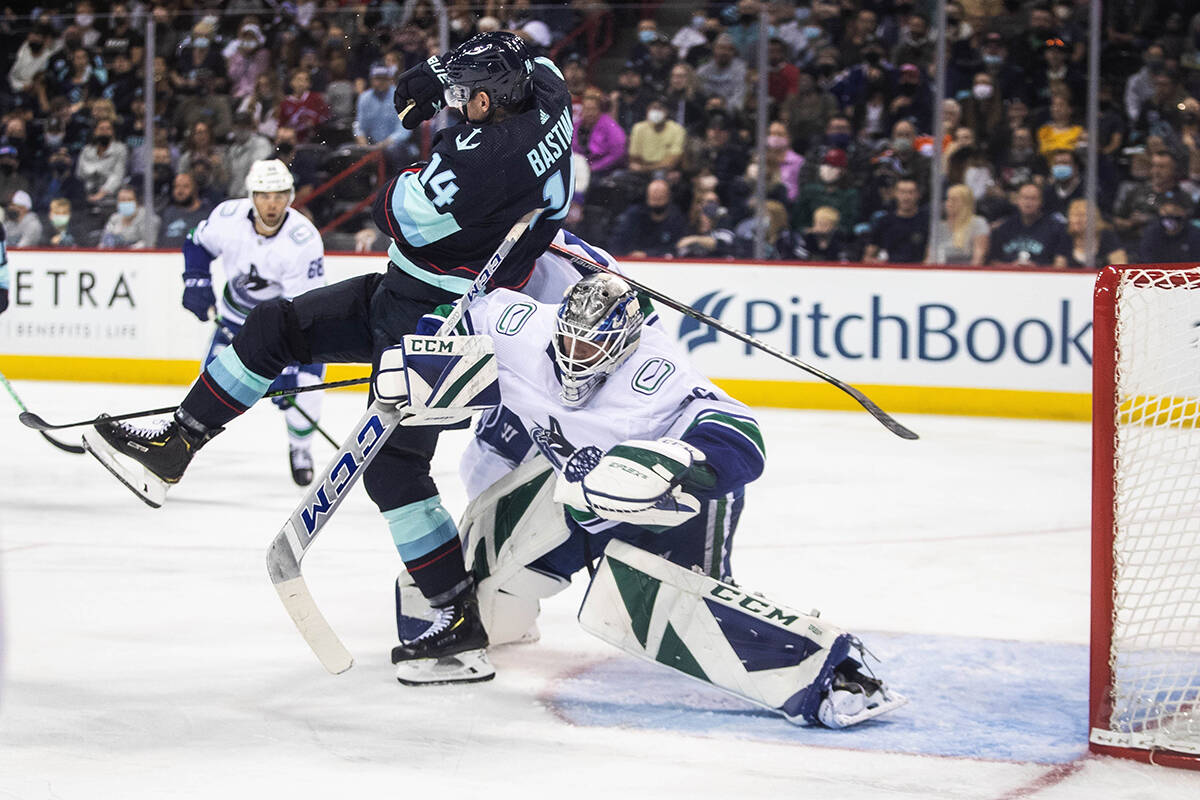 Vancouver Canucks' goalie Arturs Silovs clears Seattle Kraken's Nathan Bastian in the second period of an NHL preseason hockey game Sunday, Sept. 26, 2021, in Spokane, Wash. (Dean Rutz/The Seattle Times via AP)