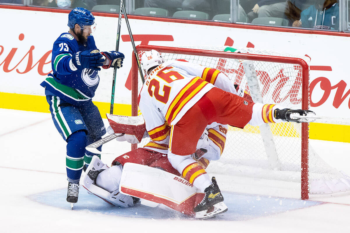 Calgary Flames' Michael Stone (26) collides with teammate, goalie Daniel Vladar, of the Czech Republic, as Vancouver Canucks' Justin Dowling, left, watches during the second period of a pre-season NHL hockey game in Abbotsford on Monday, Sept. 27, 2021. THE CANADIAN PRESS/Darryl Dyck