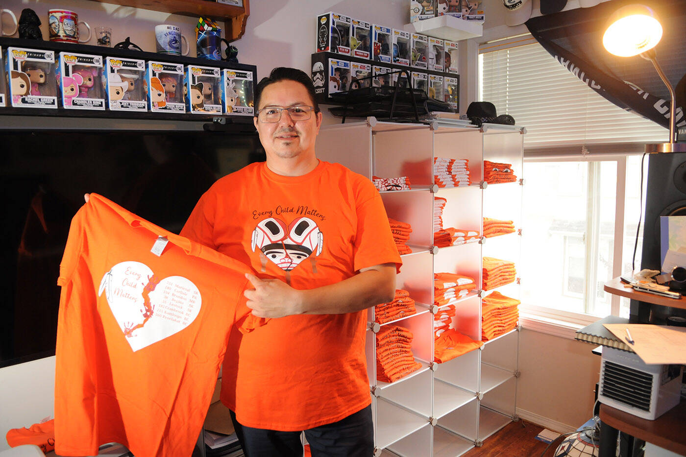 Shawn E. Baginski has been selling orange shirts he designed with all proceeds going to survivors of residential schools. He is pictured here in his Chilliwack home on Sept. 28, 2021. (Jenna Hauck/ Chilliwack Progress)