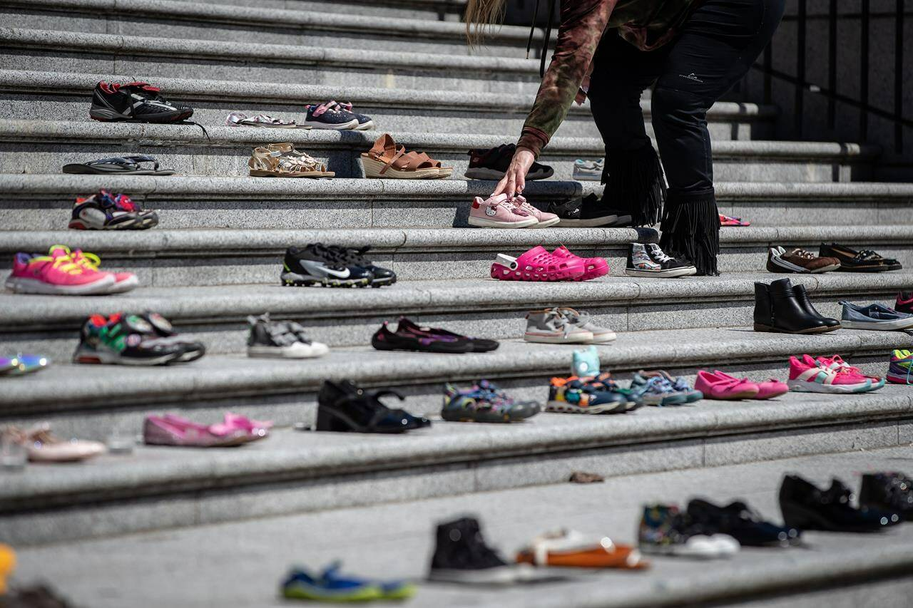 A woman places one of 215 pairs of children's shoes on the steps of the Vancouver Art Gallery as a memorial to the 215 children whose remains have been found buried at the site of a former residential school in Kamloops, in Vancouver, B.C., Friday, May 28, 2021. When the Tk'emlúps te Secwe̓pemc Nation announced the discovery of 215 unmarked graves found at the site of a former residential school in Kamloops, B.C., Canadians had to face the horrific realities Indigenous children and youth had to live while being forced to attend residential schools. THE CANADIAN PRESS/Darryl Dyck