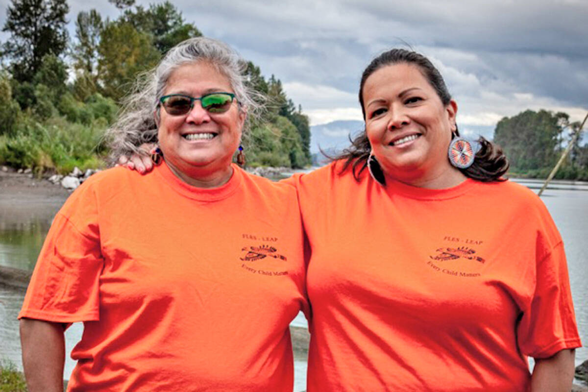 Fern Gabriel (left) and Phyllis Atkins of the Kwantlen First Nation model the orange shirts they helped create for Truth and Reconciliation day as part of a fundraiser to add Indigenous history and cultural resources to the Fort Langley Elementary School library. (Byron Smith/Special to Langley Advance Times)