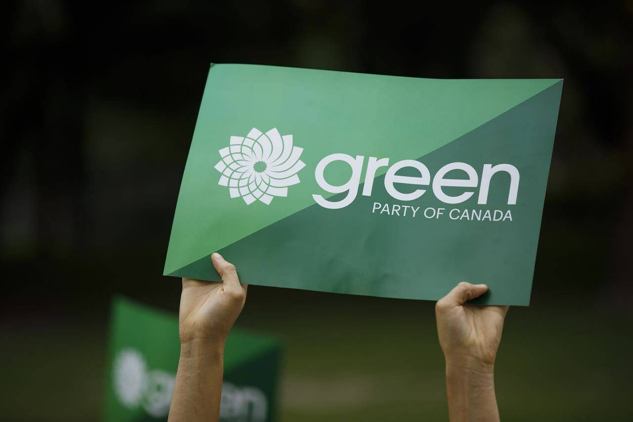 A supporter holds a sign for the Green Party of Canada as a group of candidates and supporters marched towards a discussion on climate in Toronto on September 3, 2019. THE CANADIAN PRESS/Cole Burston