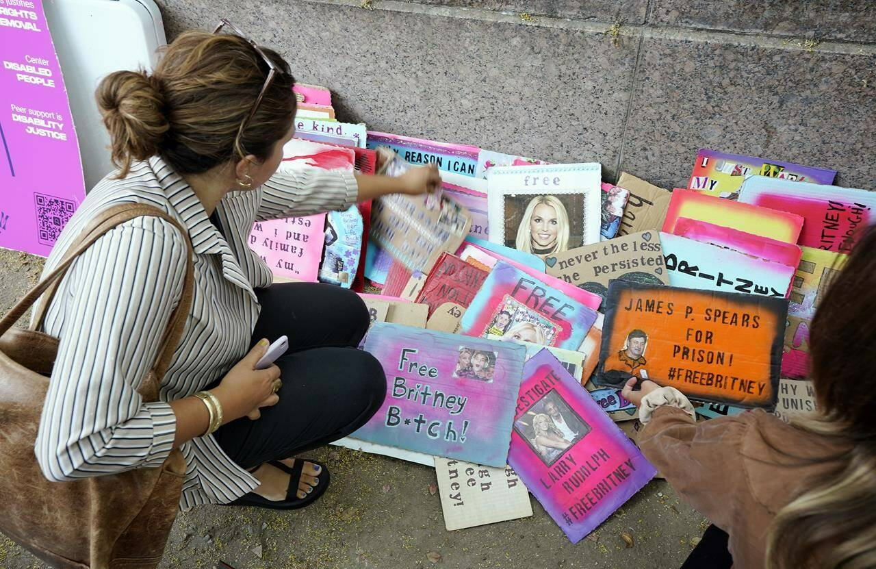 Britney Spears supporters peruse signs on a sidewalk outside the Stanley Mosk Courthouse, Wednesday, Sept. 29, 2021, in Los Angeles. A Los Angeles judge will hear arguments at a hearing Wednesday over removing Spears' father from the conservatorship that controls her life and money and whether the legal arrangement should be ended altogether. (AP Photo/Chris Pizzello)