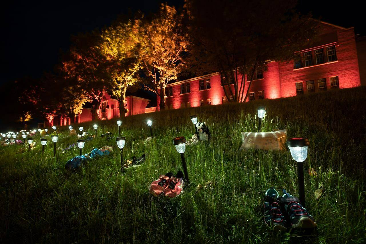 Shoes are placed on the lawn outside the former Kamloops Indian Residential School to honour 215 children after it was announced that ground-penetrating radar had detected unmarked graves near the facility in Kamloops, B.C., on June 4, 2021. THE CANADIAN PRESS/Darryl Dyck