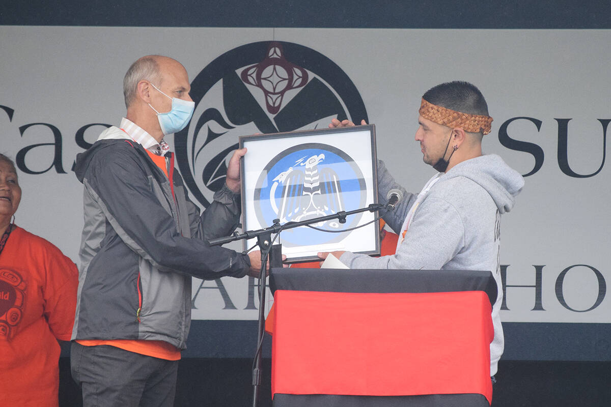Wahmeesh Ken Watts, elected Chief Councillor for Tseshaht First Nation, presents Tsuma-as Elementary School principal Ron Behnke with a piece of artwork for the school during the renaming ceremony on Sept. 29. (ELENA RARDON / ALBERNI VALLEY NEWS)