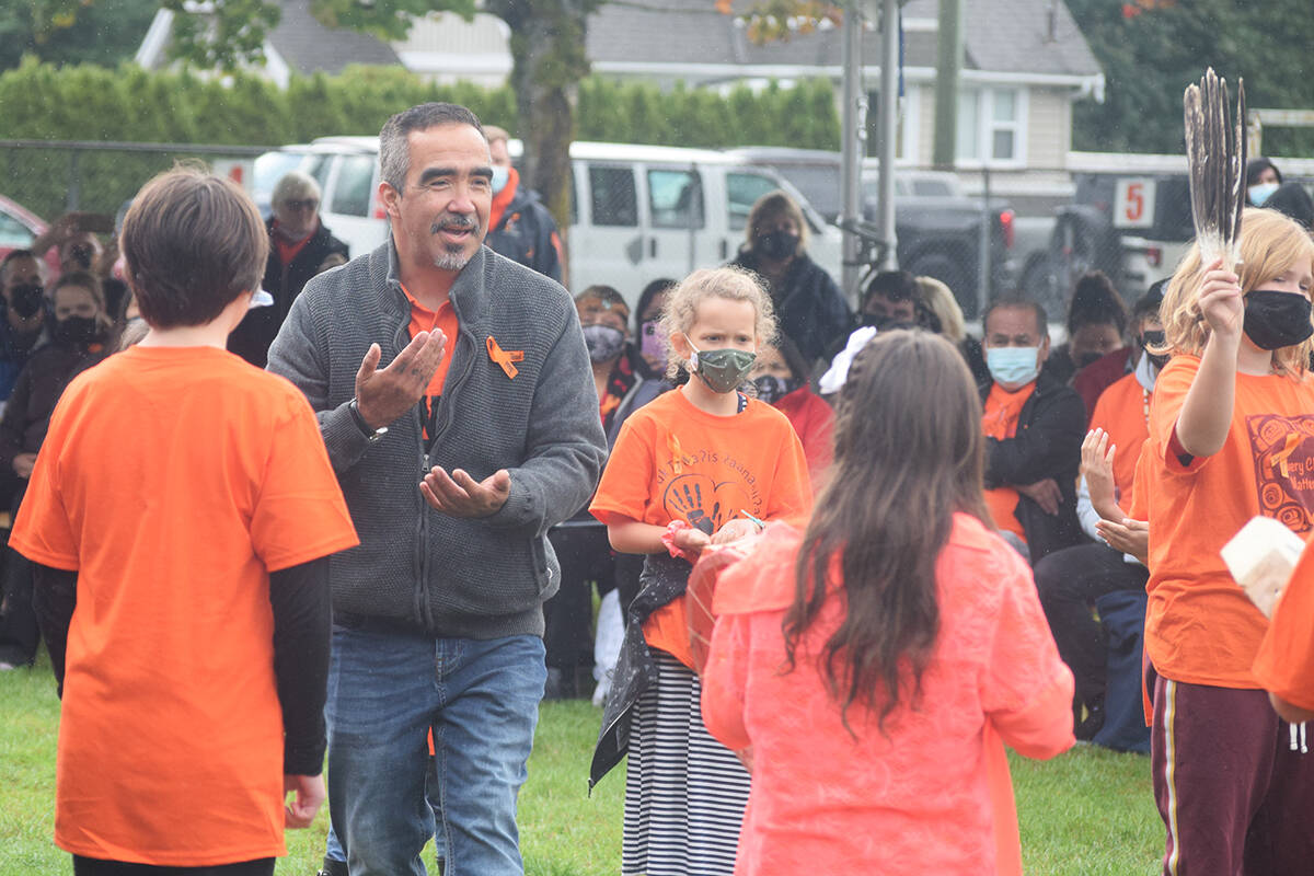 Nuu-chah-nulth Education Worker Aaron Watts leads Tsuma-as Elementary School students as they perform a Nuu-chah-nulth celebration song during the unveiling of Tsuma-as Elementary School's new name. (ELENA RARDON / ALBERNI VALLEY NEWS)