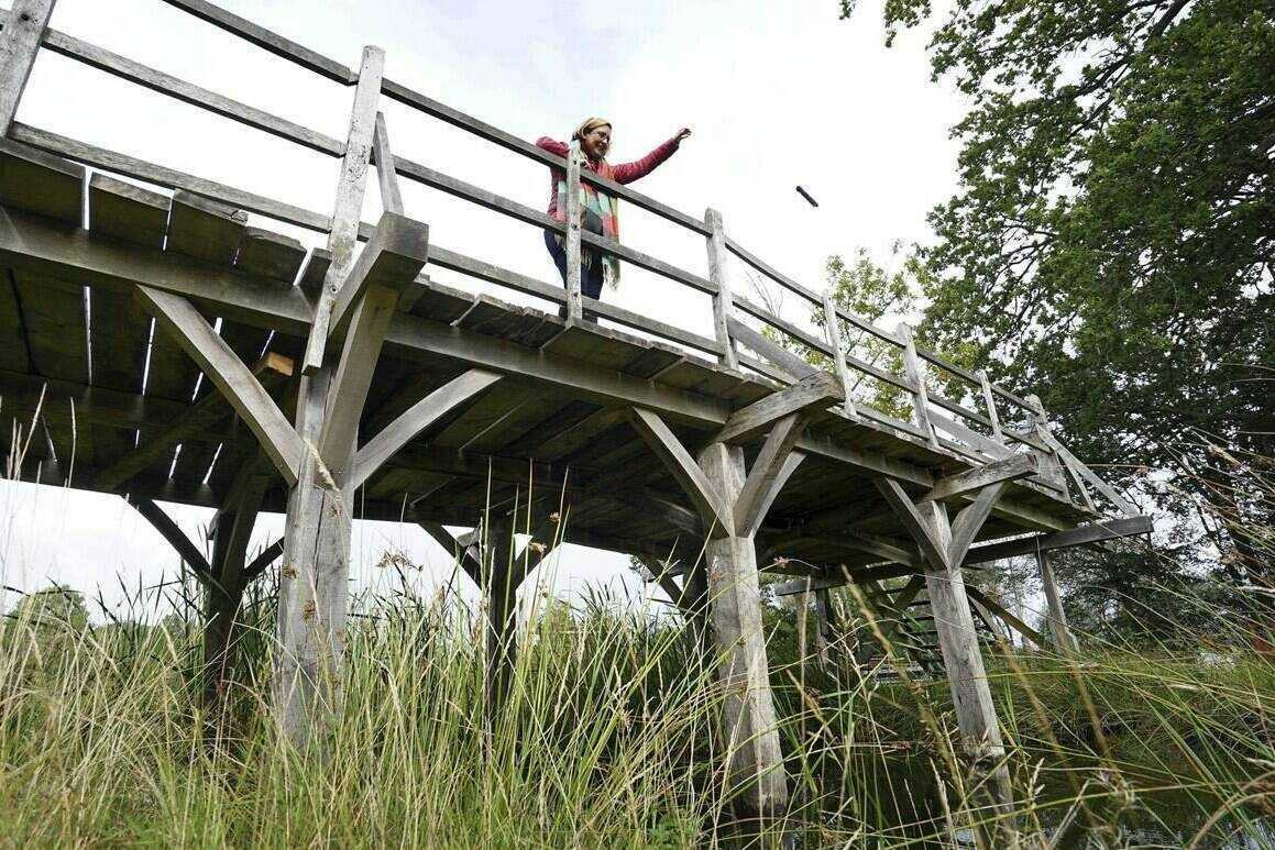 """Silke Lohmann of Summers Place Auctions stands on the original Poohsticks Bridge from Ashdown Forest, featured in A.A. Milne's Winnie the Pooh books and E.H. Shepard's illustrations, near its original location in Tonbridge, Kent, England, Thursday, Sept. 30, 2021. The adventures of the honey-loving bear """"Winnie the Pooh"""" have captivated children and their parents for nigh on 100 years. Fans now have a chance to own a central piece of Pooh's history, when a countryside bridge from the south of England goes up for auction next week. The author of the hugely popular Pooh series of books, A. A. Milne, often played with his son, Christopher Robin, at the bridge in the 1920s. The bridge became a regular setting for the adventures of Pooh and his friends in the series that launched in 1926. The auctioneers have said there's been interest from around the world, but hoped that it stays local. (Gareth Fuller/PA via AP)"""
