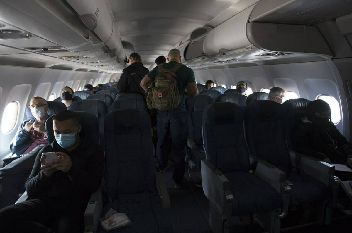 Passengers wear protective face masks and are physically distanced on a flight from Calgary to Vancouver, Tuesday, June 9, 2020. The union representing flight attendants at Canada's major airlines says reducing on-board food and drink service might help combat passenger bad behaviour in the skies. THE CANADIAN PRESS/Jonathan Hayward