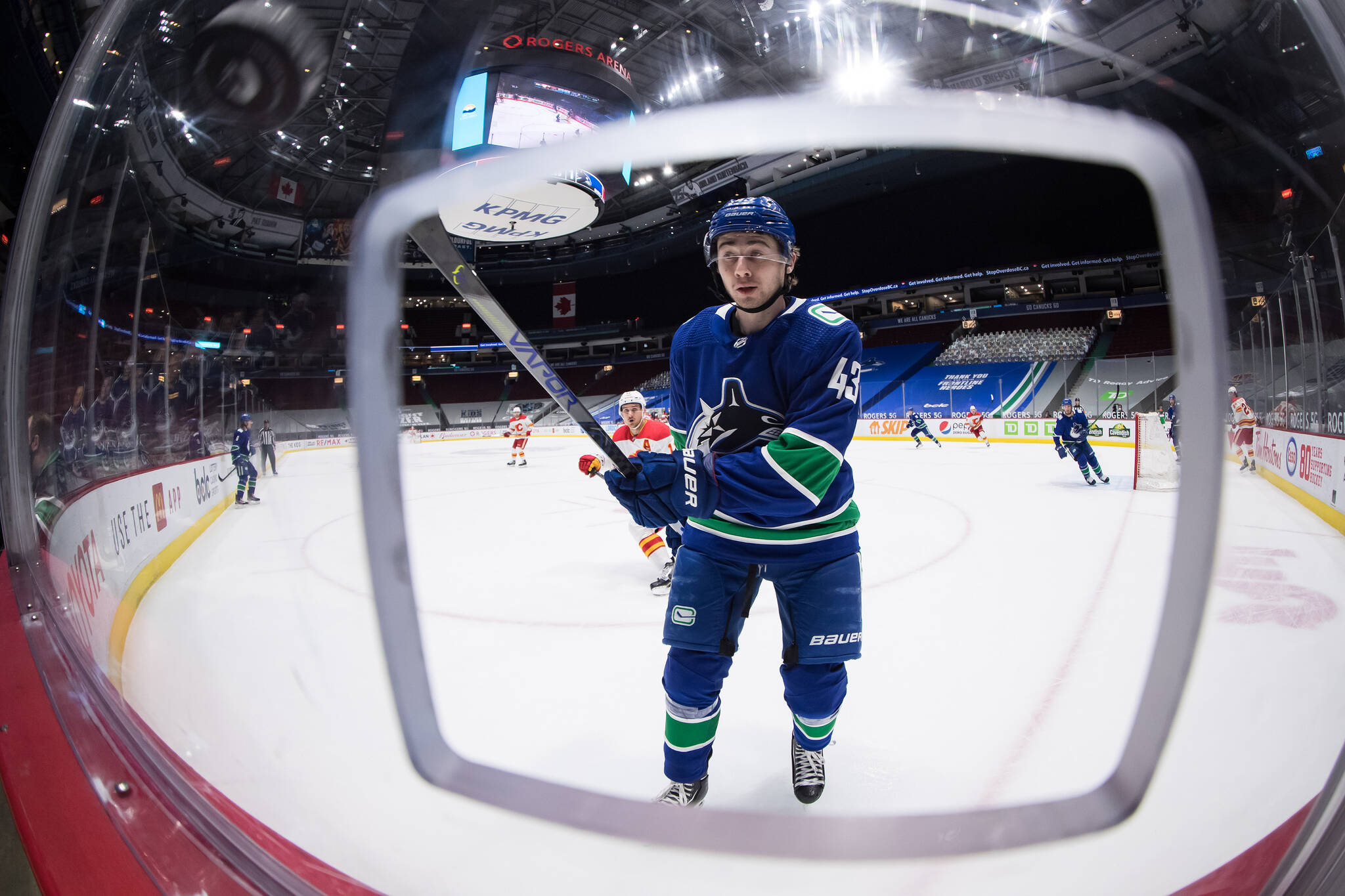 Vancouver Canucks' Quinn Hughes reaches for the puck as it bounces off the glass after being shot around the boards during first period NHL hockey action against the Calgary Flames in Vancouver, on Tuesday, May 18, 2021. THE CANADIAN PRESS/Darryl Dyck