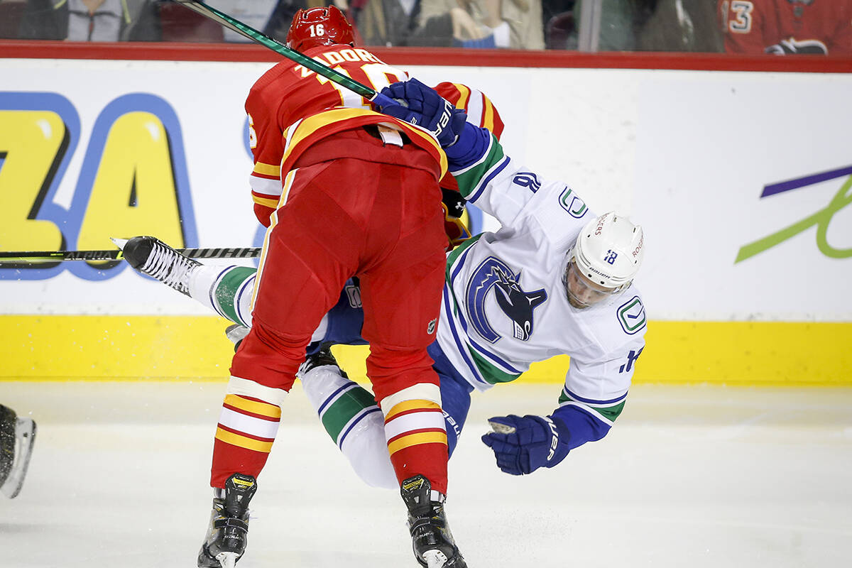 Vancouver Canucks' Jason Dickinson, right, is checked by Calgary Flames' Nikita Zadorov during second period NHL pre-season hockey action in Calgary, Friday, Oct. 1, 2021.THE CANADIAN PRESS/Jeff McIntosh