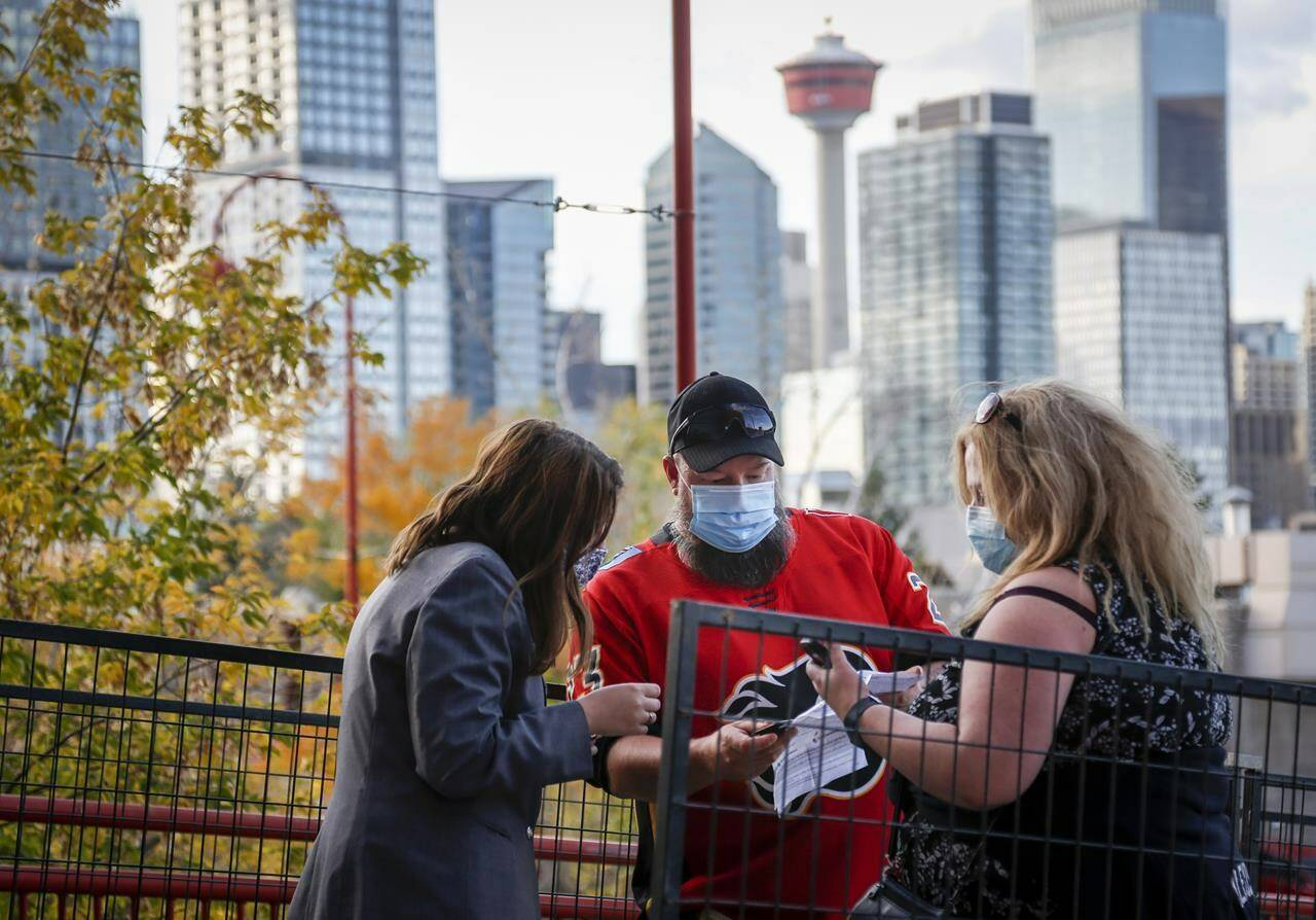 Calgary Flames fans have their COVID-19 vaccination proof checked before entering the Saddledome for pre-season NHL hockey action in Calgary, Alta., Sunday, Sept. 26, 2021. Canadians overwhelmingly support the idea of requiring vaccine passports to gain admittance to public places such as restaurants, bars and gyms, a new poll suggests. THE CANADIAN PRESS/Jeff McIntosh