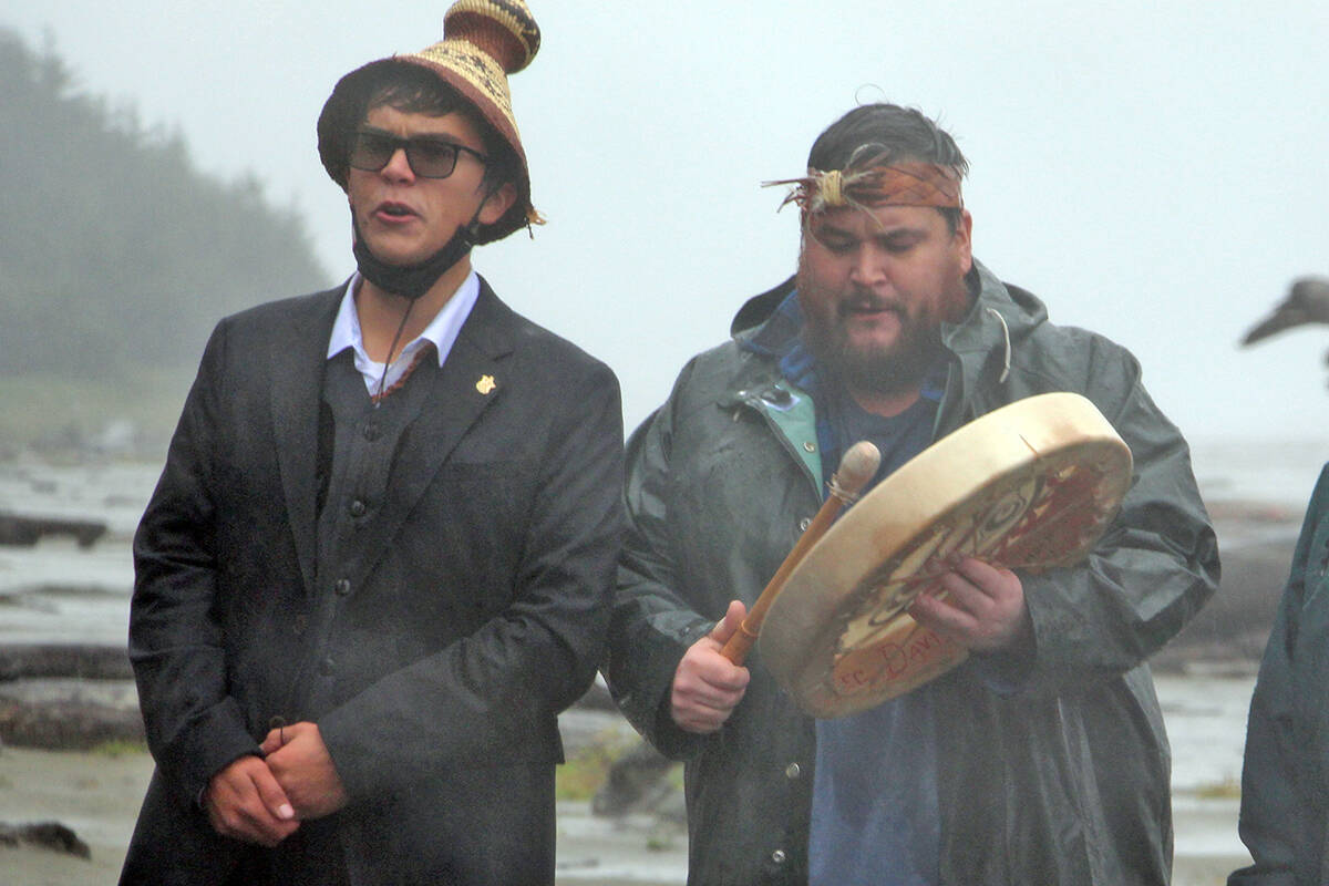 Tla-o-qui-aht First Nation members Timmy Masso and Hjalmer Wenstob lead a gathering outside the Tofino beachfront property Prime Minister Justin Trudeau is currently staying in to demand an apology on a rainy Saturday evening. (Andrew Bailey photo)