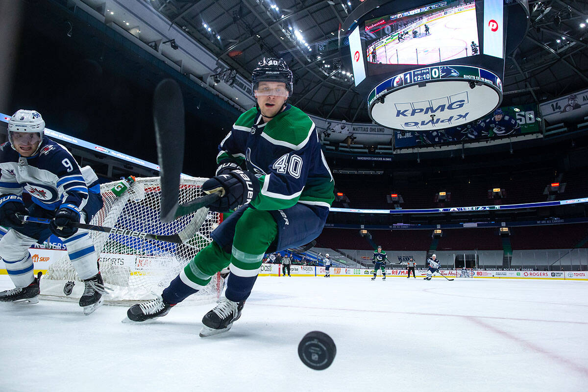 Vancouver Canucks' Elias Pettersson (40), of Sweden, reaches for the puck in front of Winnipeg Jets' Andrew Copp (9) during the second period of an NHL hockey game in Vancouver, on Friday, February 19, 2021. THE CANADIAN PRESS/Darryl Dyck