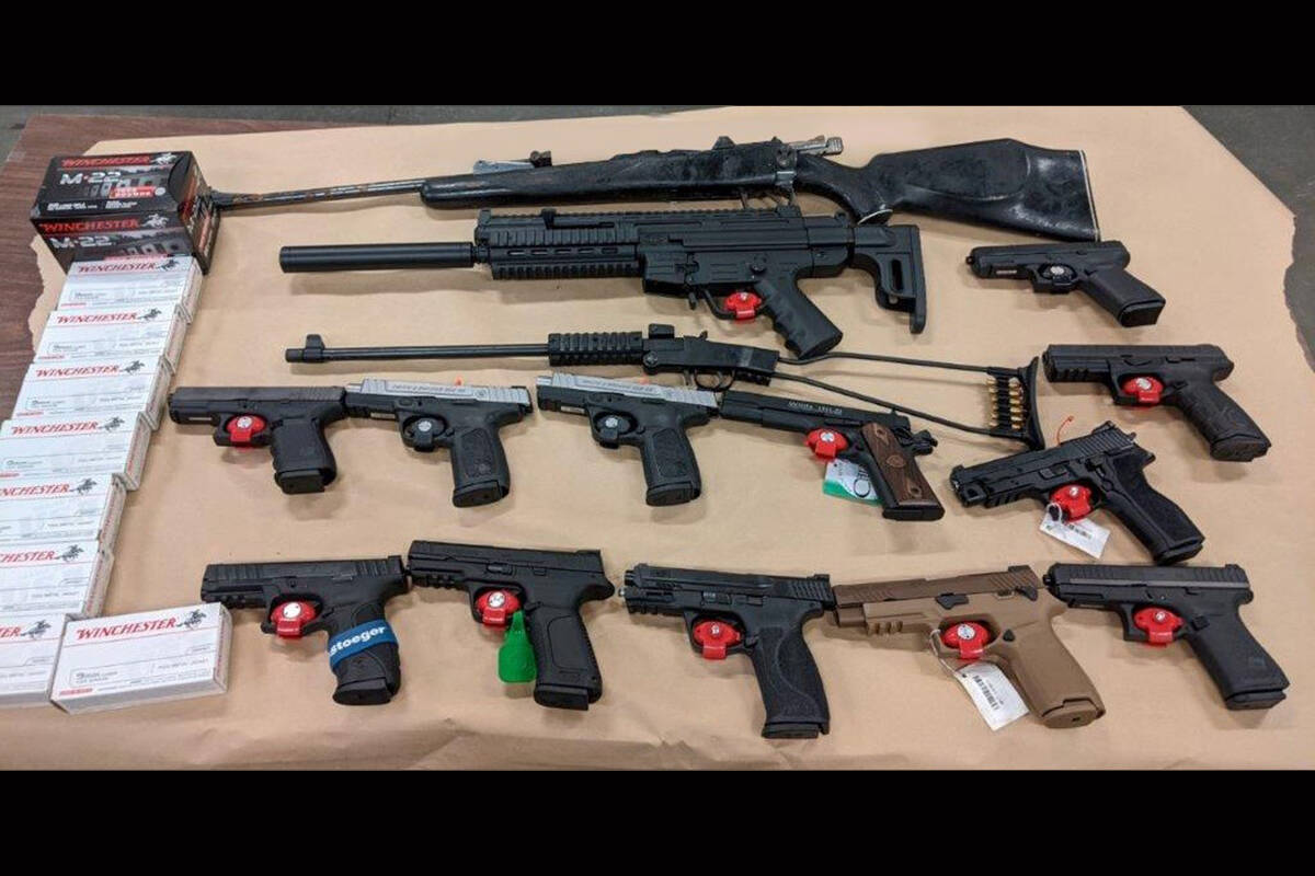Some of the weapons and ammunition seized as a result of a January raid in Langley, which has now led to charges against two men. (BCCFSEU)