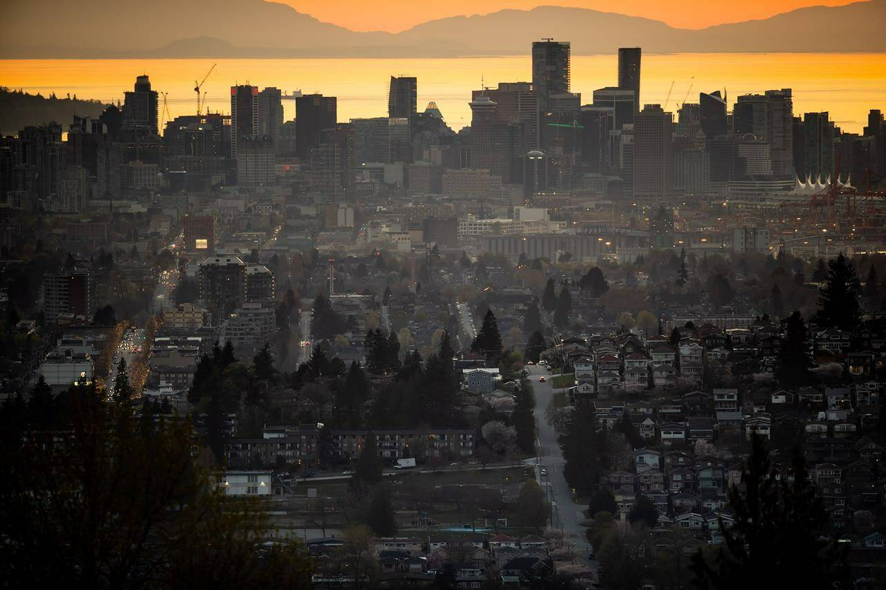 The downtown Vancouver skyline is seen at sunset, as houses line a hillside in Burnaby, B.C., on Saturday, April 17, 2021. Home sales across Metro Vancouver remained well above the 10-year average in September, but the Real Estate Board of Greater Vancouver says prices haven't climbed as sharply. THE CANADIAN PRESS/Darryl Dyck