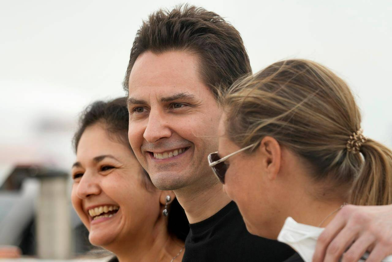 Michael Kovrig, centre, embraces his wife Vina Nadjibulla, left, and sister Ariana Botha after arriving at Pearson International Airport in Toronto, Saturday, Sept. 25, 2021. Two Canadians who were imprisoned in China for nearly three years are home. THE CANADIAN PRESS/Jeff McIntosh