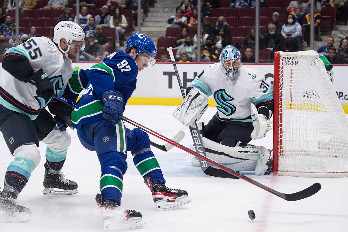 Seattle Kraken's Jeremy Lauzon (55) checks Vancouver Canucks' Vasily Podkolzin (92), of Russia, as Seattle's goalie Philipp Grubauer (31), of Germany, watches during the second period of a pre-season NHL hockey game in Vancouver, on Tuesday, October 5, 2021. THE CANADIAN PRESS/Darryl Dyck