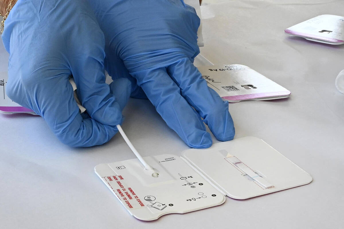 A rapid COVID-19 test swab is processed at Palos Verdes High School in Palos Verdes Estates, Calif., Tuesday, Aug. 24, 2021. The district is encouraging all students and staff to test before the first day of school, August 25, and there are three sites for the drive-up testing. (Brittany Murray/The Orange County Register via AP)