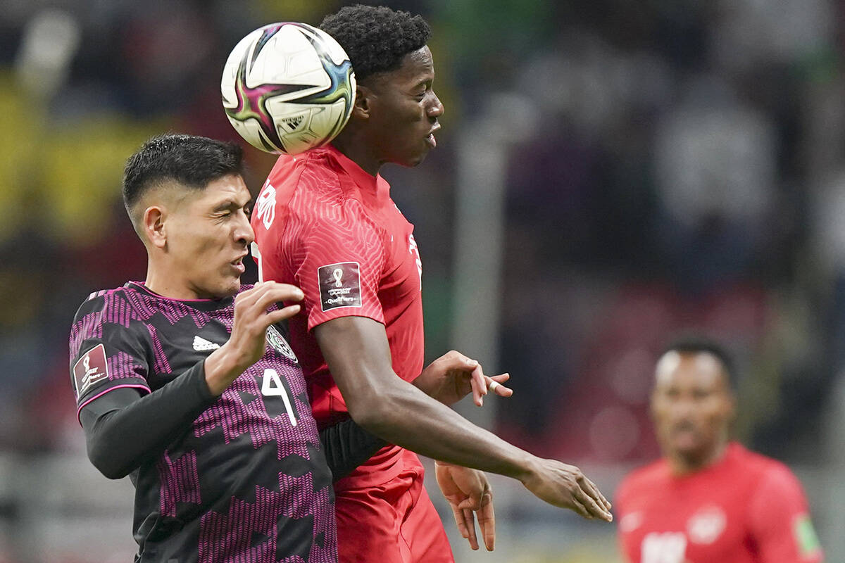 Canada's Jonathan David, right, and Mexico's Edson Alvarez go for a header during a qualifying soccer match for the FIFA World Cup Qatar 2022 in Mexico City, Thursday, Oct. 7, 2021. (AP Photo/Fernando Llano)