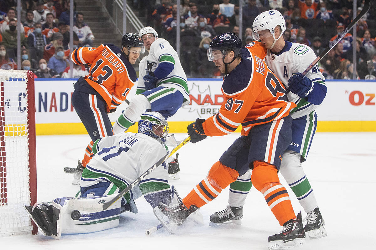 Vancouver Canucks' goalie Jaroslav Halak (41) makes the save on Edmonton Oilers' Connor McDavid (97) as Elias Pettersson (40) defends during second period NHL pre-season action in Edmonton on Thursday, October 7, 2021.THE CANADIAN PRESS/Jason Franson
