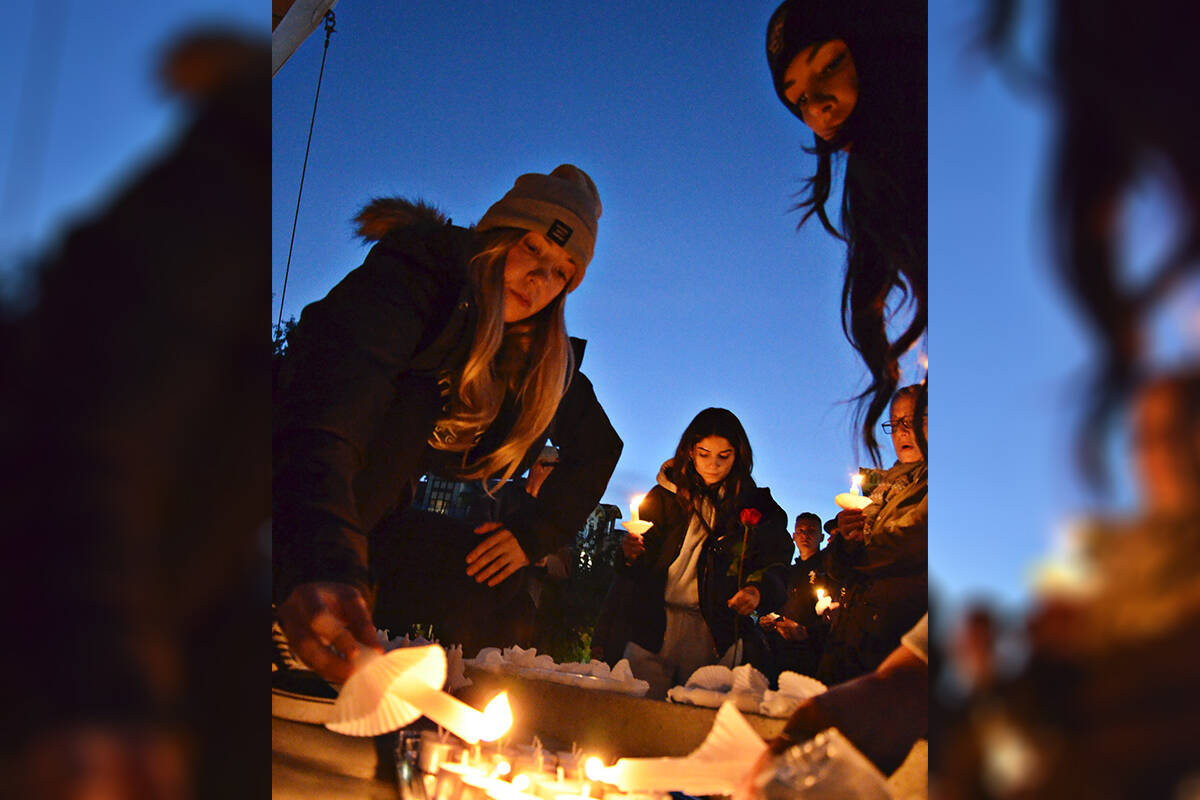 Ashlynd Edwards and Marissa Quinlan helped light candles at a vigil for Devon Goodrick. He is missing and family and friends gathered in Douglas Park on Thursday evening to show support for his loved ones. (Heather Colpitts/Langley Advance Times)