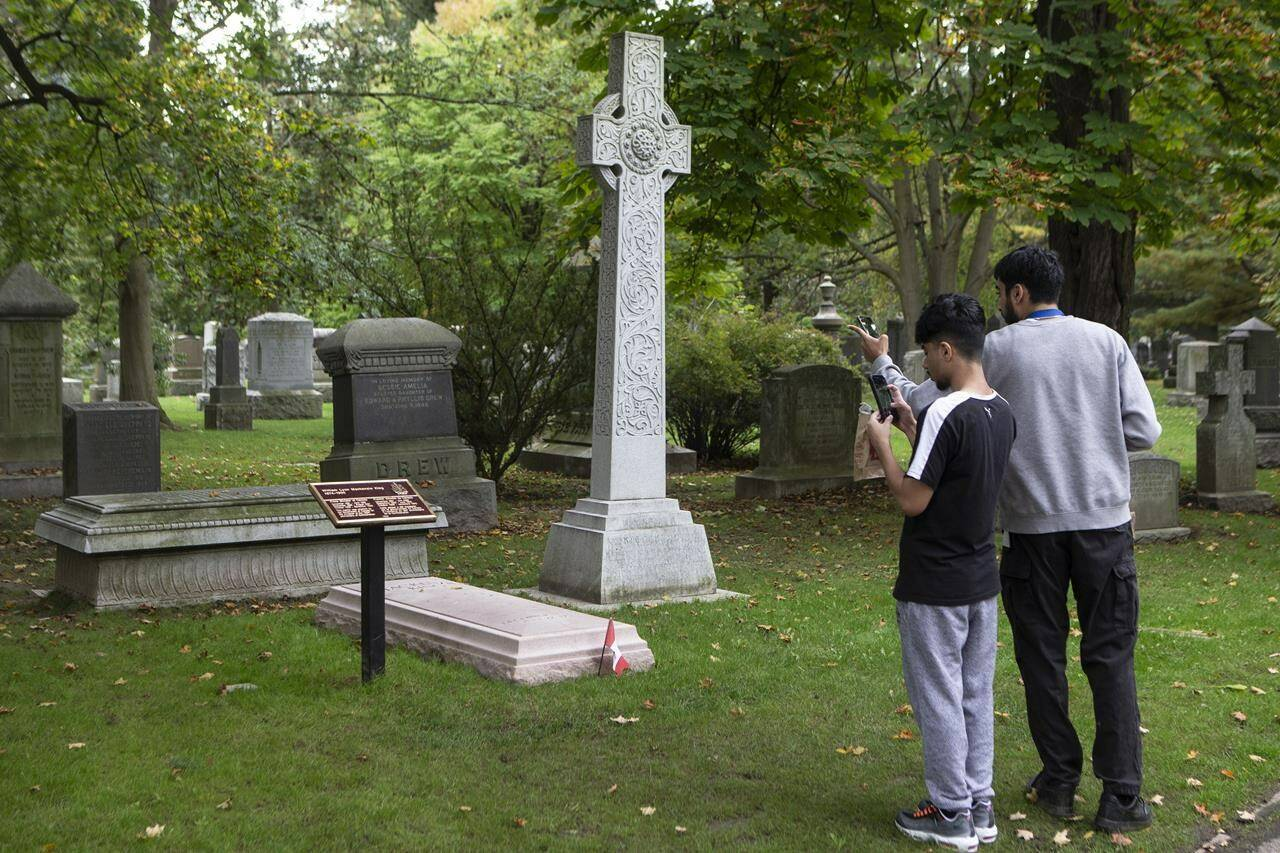 Passers-by stop to take a photo of the grave of former Canadian prime minister Mackenzie King in Toronto's Mount Pleasant Cemetery on Friday, October 8, 2021. THE CANADIAN PRESS/Chris Young