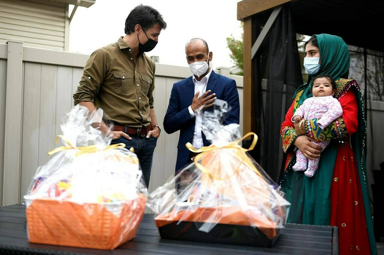 Prime Minister Justin Trudeau speaks with Obaidullah Rahimi, right, his wife Arezoo, and daughter Hawa, 2 months, after assembling care packages for the recently resettled Afghan family for Thanksgiving in Ottawa, on Saturday, Oct. 9, 2021. Obaidullah Rahimi worked at the Canadian Embassy in Afghanistan; his family is one of 22 resettled Afghan families in the Ottawa area. THE CANADIAN PRESS/Justin Tang