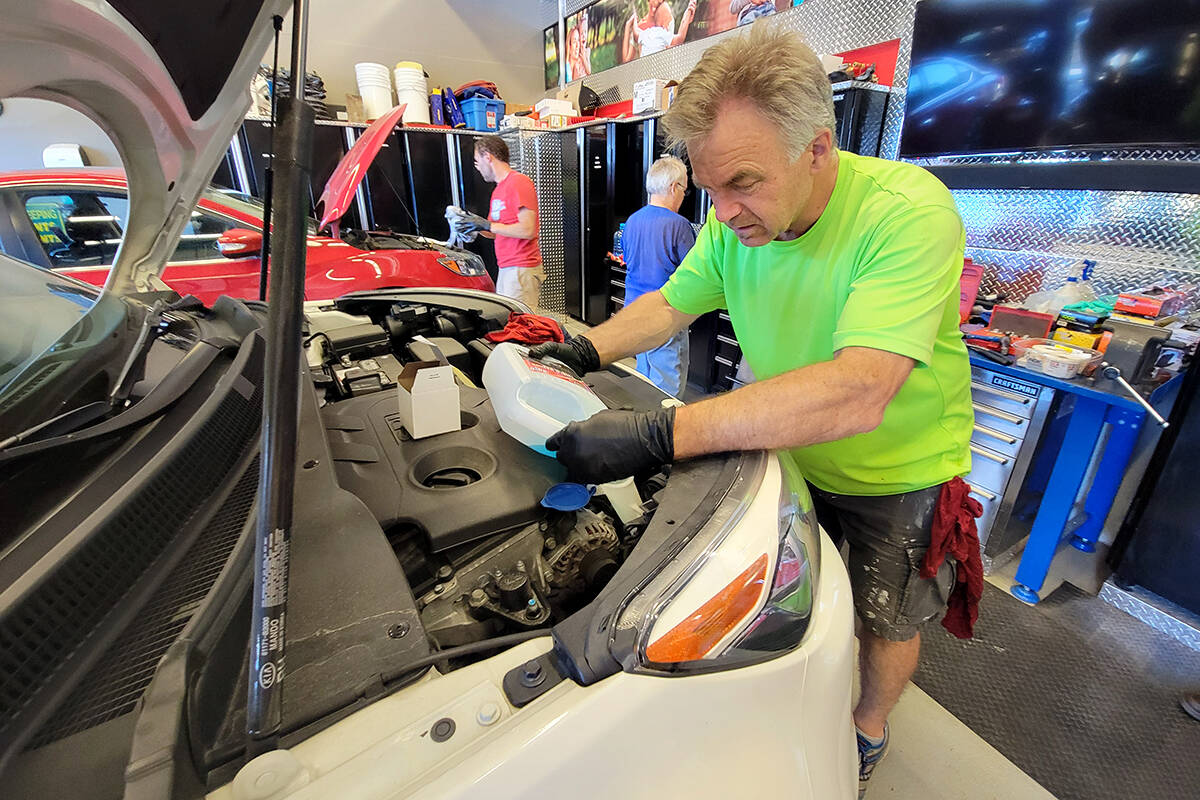 A volunteer works on a car at the semi-annual free oil change for single moms offered by the Acts Of Kindness group at Langley's Church In The Valley on Sunday, June 27. (Dan Ferguson/Black Press Media)