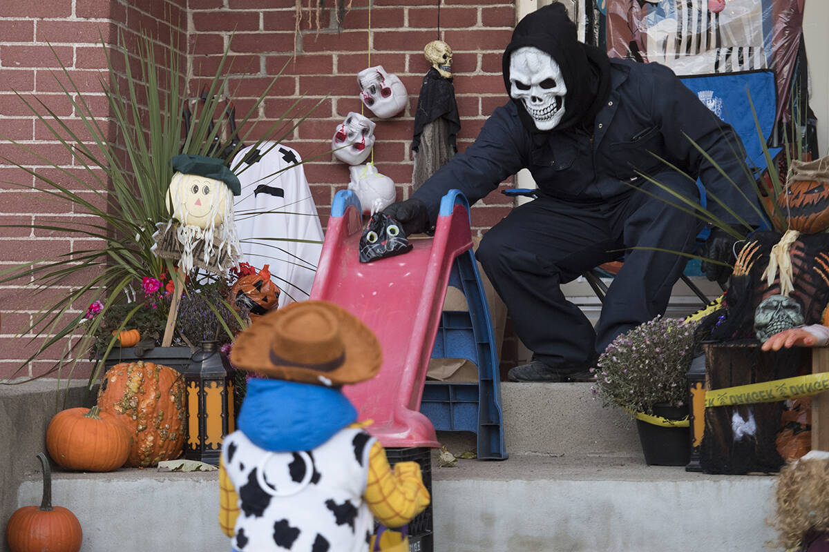 FILE – Alessandro Priolo slides a bag of candy to a young boy at his house on Halloween in Montreal, Saturday, October 31, 2020, as the COVID-19 pandemic continues in Canada and around the world. THE CANADIAN PRESS/Graham Hughes