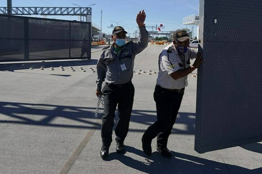 Mexican security officers open the main gate of the international border bridge that connects Del Rio, Texas and Ciudad Acuna, Mexico, after its partial reopening Saturday, Sept. 25, 2021. A new trilateral poll suggests U.S. residents are far more worried about reopening the land border with Mexico than they are about letting Canadians drive into the country.THE CANADIAN PRESS/AP/Fernando Llano