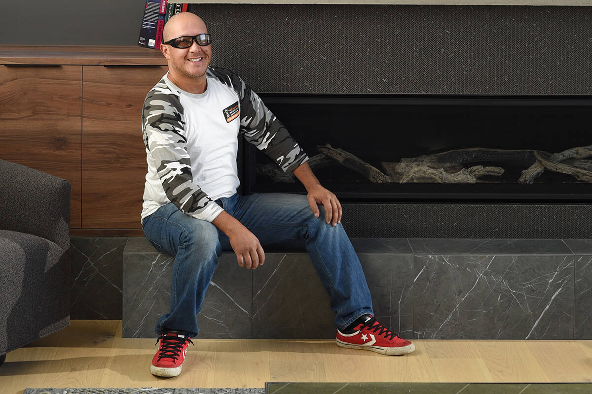 Daniel Caicedo, owner of Victoria Restorations, sits next to a fireplace his company provided the chimney finish for in a Sidney home. Don Denton photograph
