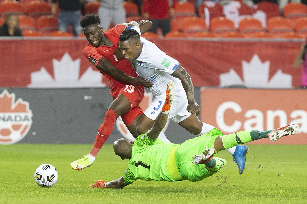 Canada's Alphonso Davies (left) runs around Panama goalkeeper Luis Mejia as Harold Cummings looks on during first half World Cup qualifying action in Toronto, on Wednesday, October 13, 2021. THE CANADIAN PRESS/Chris Young